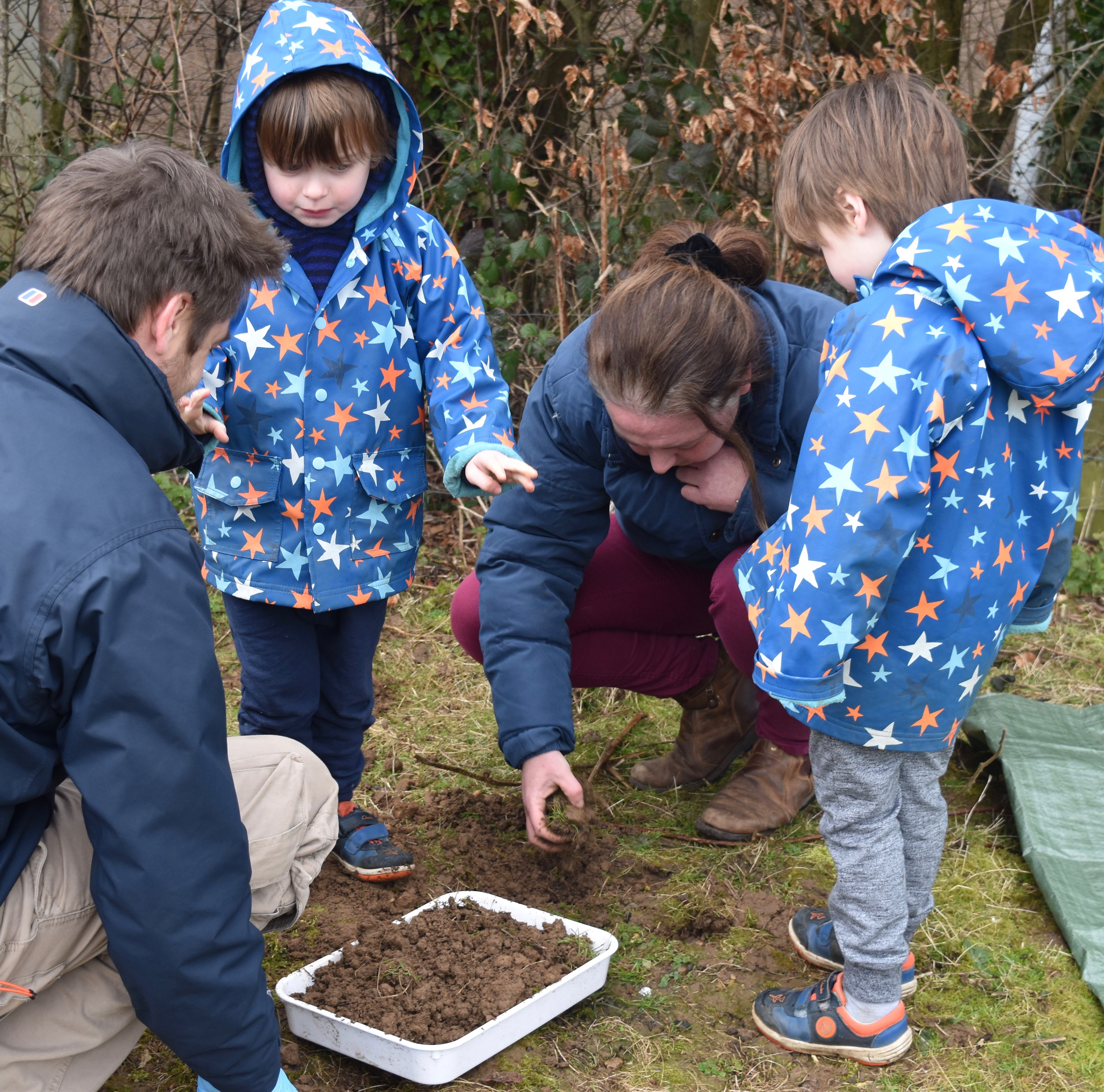 children and adults looking for worms